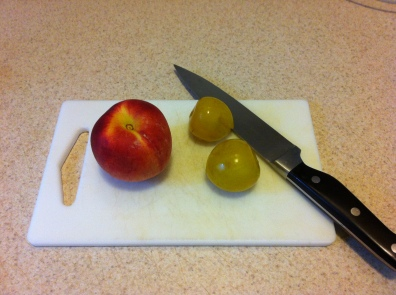 A peach, and two of the smallest plums in the world