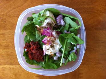 On a spinach salad with olive oil, red onion, and sundried tomato paste